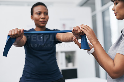 Buy stock photo Shot of a physiotherapist helping a patient work through her recovery with resistance bands