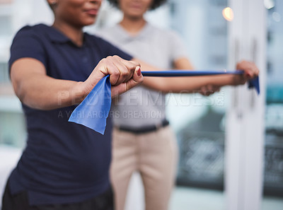 Buy stock photo Closeup shot of a physiotherapist helping a patient work through her recovery with resistance bands