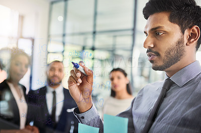 Buy stock photo Shot of a businessman writing notes on a glass wall while brainstorming with his colleagues in an office