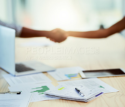Buy stock photo Closeup shot of paperwork on a table in an office with two businesspeople shaking hands in the background