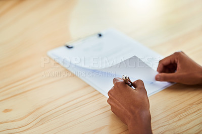 Buy stock photo Closeup shot of an unrecognizable businesswoman filling in paperwork on a clipboard in an office