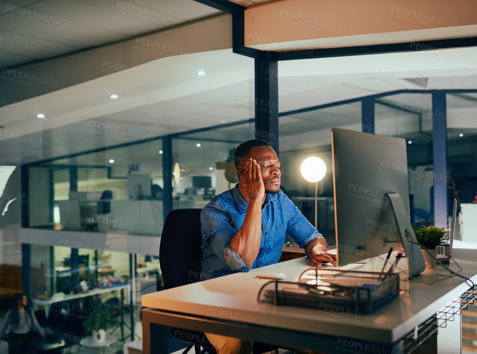 Buy stock photo Cropped shot of a young handsome businessman experiencing a headache while working late in the office