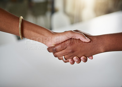 Buy stock photo High angle shot of two unrecognizable businesswomen shaking hands while standing in their office