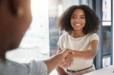 Buy stock photo Cropped shot of two businesswomen shaking hands during a meeting in the boardroom