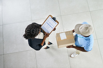 Buy stock photo High angle shot of a young woman signing for her delivery from the courier in an office