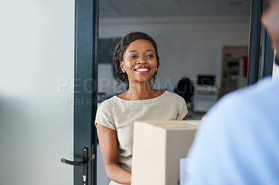 Buy stock photo Shot of a young woman receiving a package from a delivery man in a modern office
