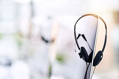 Buy stock photo Shot of a headset hanging on a computer screen in an office