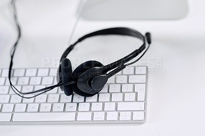 Buy stock photo Shot of a headset lying on a keyboard in an office