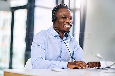 Buy stock photo Shot of a happy young man working in a modern call centre