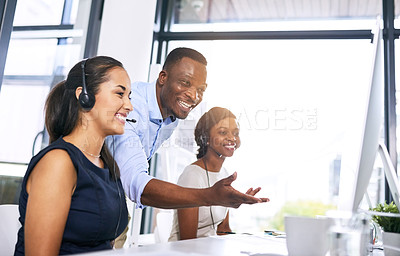 Buy stock photo Shot of a young man helping his colleague in a modern call centre