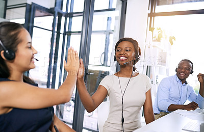Buy stock photo Shot of  happy young women giving each other a high five in a modern call centre