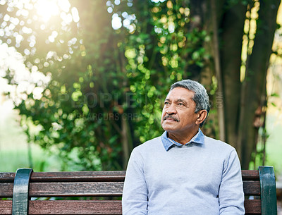 Buy stock photo Cropped shot of a handsome senior man looking thoughtful while sitting in the park