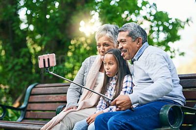 Buy stock photo Cropped shot of an adorable little girl taking selfies with her grandparents while enjoying the day outdoors