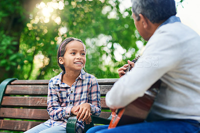 Buy stock photo Cropped shot of an adorable little girl learning how to play the guitar while enjoying the day outdoors with her granddad