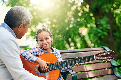 Buy stock photo Cropped portrait of an adorable little girl learning how to play the guitar while enjoying the day outdoors with her granddad