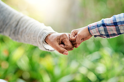 Buy stock photo Cropped shot of an unrecognizable little girl and her grandmother fist bumping while enjoying the day outdoors
