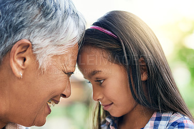 Buy stock photo Cropped shot of an adorable little girl standing face to face with her grandmother while enjoying the day outdoors