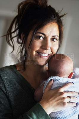 Buy stock photo Portrait of a cheerful young woman holding her little infant son at home during the day
