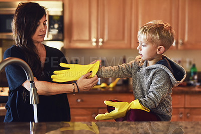 Buy stock photo Shot of a carefree young woman putting yellow washing gloves on her little boys hands to help her do the dishes at home during the day