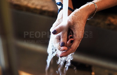 Buy stock photo Closeup of an unrecognizable woman washing her hands under a tap at home during the day
