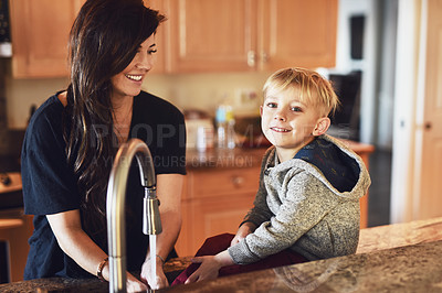 Buy stock photo Shot of a cheerful young woman washing her hands while her little boy sits next to her and contemplates at home during the day