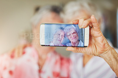 Buy stock photo Shot of two happy elderly women taking selfies together on a mobile phone