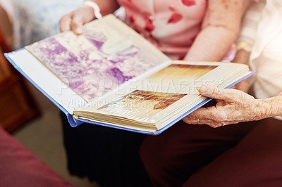 Buy stock photo Cropped shot of two elderly women looking through a photo album together