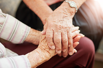 Buy stock photo Cropped shot of two senior women holding hands in a retirement home