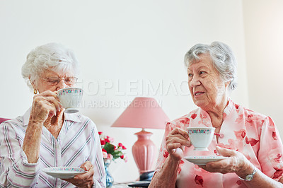 Buy stock photo Shot of two happy elderly women having tea together at home