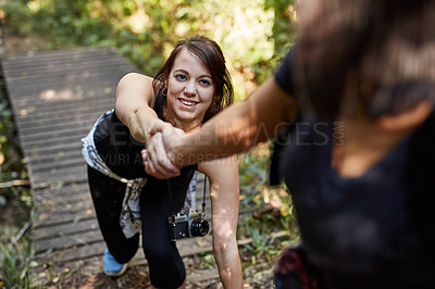 Buy stock photo Shot of a young woman being pulled up a footbridge while out hiking with her friend