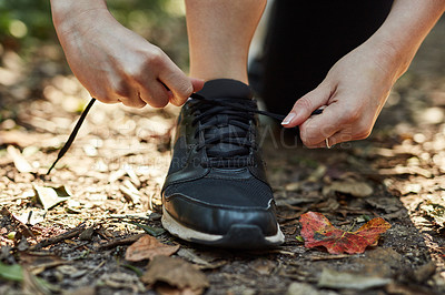Buy stock photo Cropped shot of an unrecognizable person tying his shoelaces while out hiking