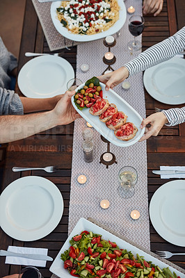 Buy stock photo High angle shot of a group of people enjoying a meal together outdoors