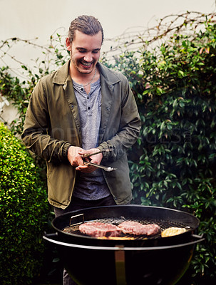Buy stock photo Cropped shot of a young man tending to the barbecue outdoors