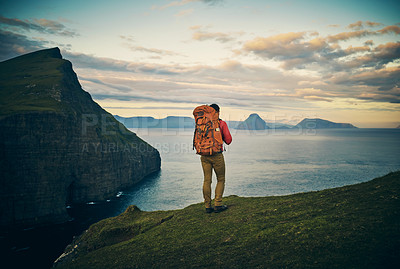 Buy stock photo Rearview shot of a carefree unrecognizable man standing on a hill looking out to a view of a lake and mountains