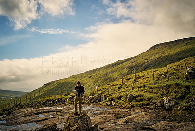 Buy stock photo Shot of a carefree young man standing on a rock while reading a map outside in nature during the day