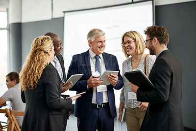 Buy stock photo Shot of a group of businesspeople talking and using digital tablets together at a convention center