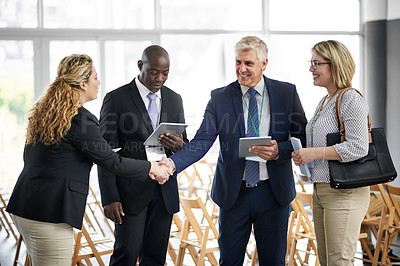 Buy stock photo Shot of a businessman and businesswoman shaking hands at a convention center surrounded by other colleagues