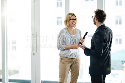 Buy stock photo Shot of a businessman and businesswoman having a discussion at a convention center