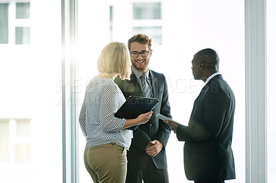 Buy stock photo Shot of a group of businesspeople chatting at a convention center