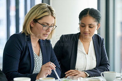 Buy stock photo Shot of two businesswomen having a meeting in the boardroom