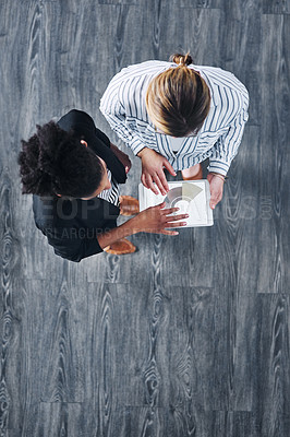Buy stock photo High angle shot of two businesswomen analyzing graphs on a digital tablet in an office