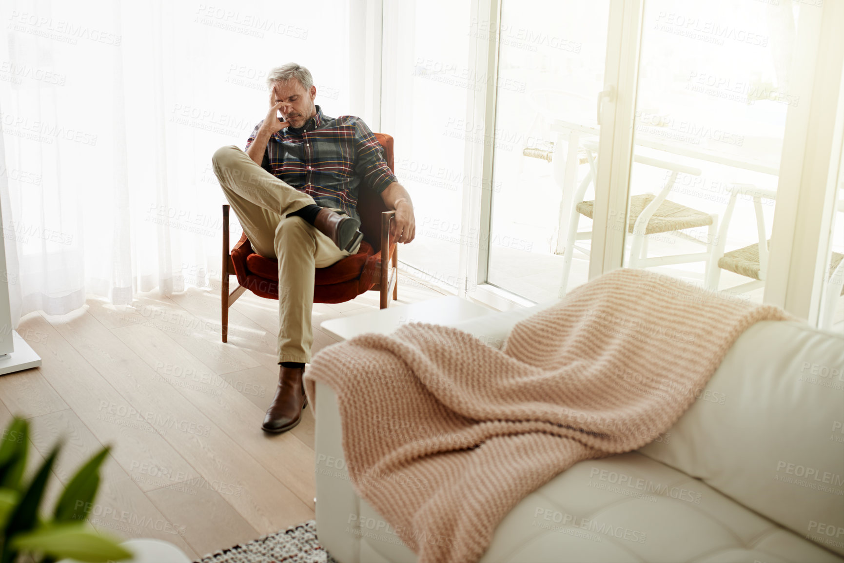 Buy stock photo Shot of a mature man sitting on a chair with his eyes closed at home