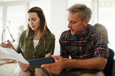 Buy stock photo Shot of a mature couple managing their budget together at home