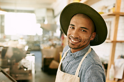 Buy stock photo Portrait of a cheerful young business owner wearing a hat while standing inside of his coffees shop during the day