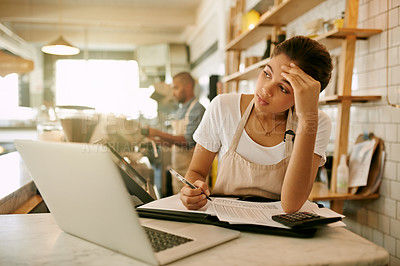 Buy stock photo Shot of a stressed out young woman working on her laptop while making notes inside of a coffee shop during  the day