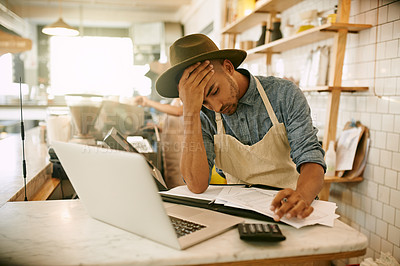 Buy stock photo Shot of a stressed out young man working on his laptop while making notes inside of a coffee shop during  the day