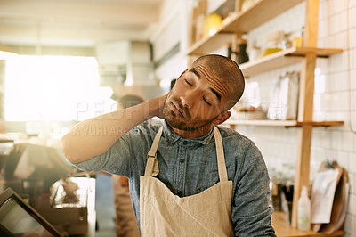 Buy stock photo Shot of a stressed out young man trying to get some paperwork done while holding his neck in discomfort inside a coffee shop during the day