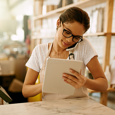 Buy stock photo Shot of a confident young woman browsing on a digital tablet while taking a call on her phone at work