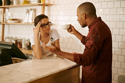 Buy stock photo Shot of a young woman serving a difficult customer in a coffee shop