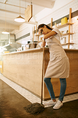 Buy stock photo Shot of a young woman mopping the floor of a coffee shop during the day
